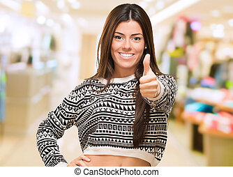 Young Woman Showing Best Of Luck Sign at a mall