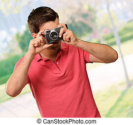 Portrait of a man taking photo, outdoor