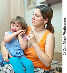 Woman scolds crying child in home
