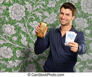 Young Man Holding Gold Bar And Euro Currency On Wallpaper