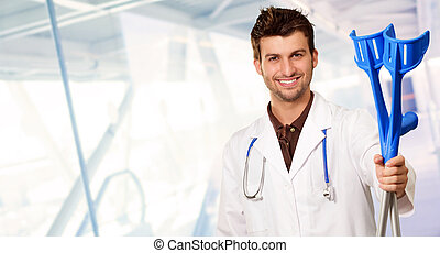 Young Doctor Holding Crouches, Indoors