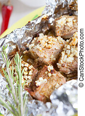 pieces of meat baked in foil in the oven, closeup
