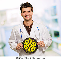 Happy Young Doctor Holding Bulls Eye, indoor