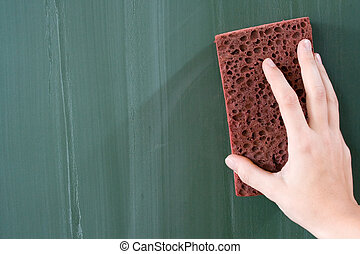 Erasing the Chalkboard - Female hand erasing a greenish...