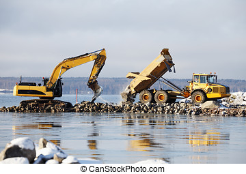 bulldozer and dredging works - bulldoxer collecting rocks...