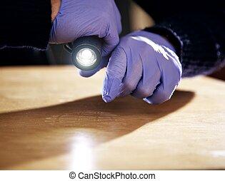 Footprint on the Floor Left by a Burglar - Hand holding a...