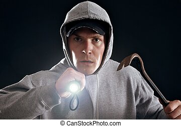 Burglar with crowbar and a flashlight ready for work