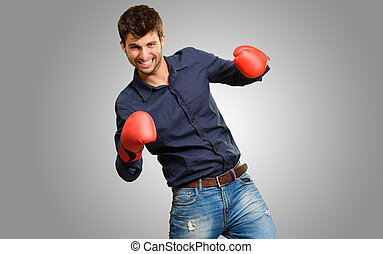 Young Man Wearing Boxing Gloves Isolated On Grey Background