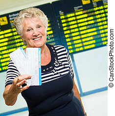 Senior Woman Holding Boarding Pass, Indoors