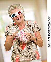 v - Senior Woman Eating Popcorn Watching 3d Movie, Indoors