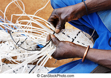 Man weaving long plastic strands - Hands of a black african...