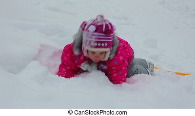 little girl playing in snow at winter