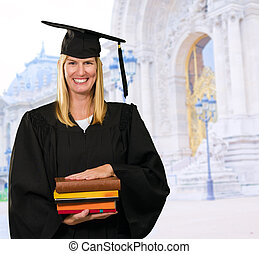 Happy Graduate Woman Holding Books in front of a university...