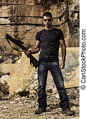 man with a shotgun - View of a man with a shotgun in jeans...