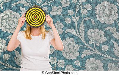 Portrait Of A Woman Holding Dartboard On Wallpaper