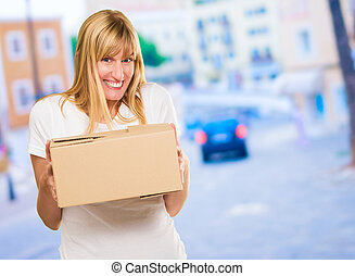 Woman Holding Cardboard box against a street background