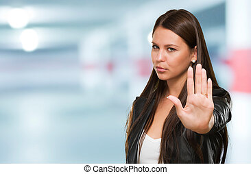 Young Woman Showing Stop Hand Gesture in a garage