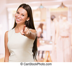 Portrait Of A Happy Young Woman Pointing At You in a shop