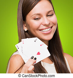 Portrait Of A Young Woman Holding Cards against a green...