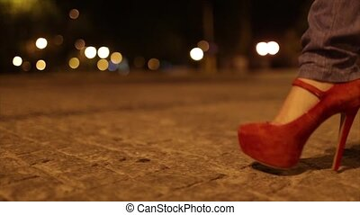 Close-up on red shoes - Girl in jeans and red shoes, seen...