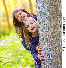 Autumn sister kid girls playing in forest trunk outdoor -...