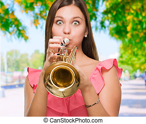 Young Woman Blowing Trumpet, outdoor