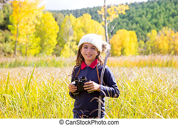Explorer binocular kid girl in yellow autumn nature outdoor