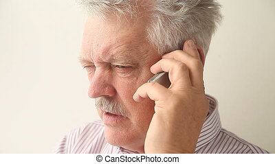 angry senior man on mobile phone - older man is upset with...