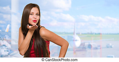 Beautiful Young Woman Blowing A Kiss at the airport