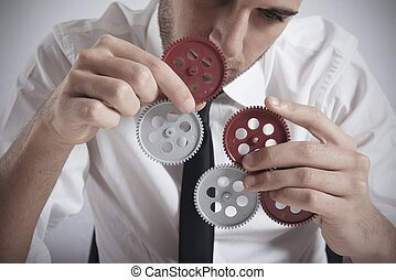 Teamwork concept with businessman working with gear