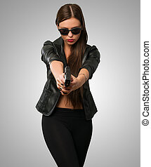 Woman Aiming With Gun against a grey background
