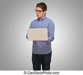 Young Man Using Laptop against a grey background