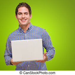 Handsome Young Man Holding Laptop against a green background