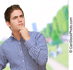 Portrait Of Young Man Thinking at a park