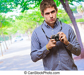Serious Man Holding Vintage Camera at a park