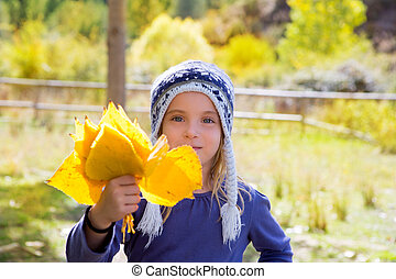 Child girl in autumn poplar forest yellow fall leaves in...