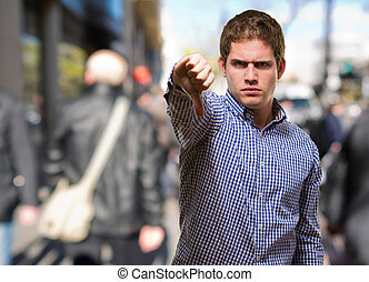 Young Man Showing His Thumb Down against a street background...