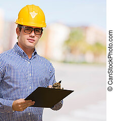 Portrait Of Engineer Holding Clipboard against a street...
