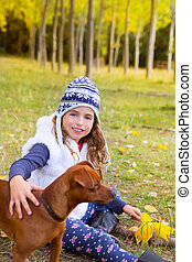 Autumn girl in poplar tree forest playing with dog sitting...