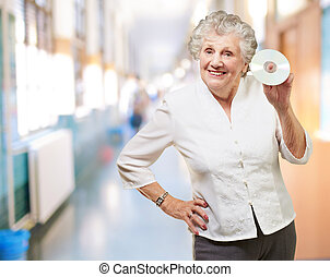 Senior woman holding cd, indoor