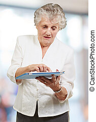 Senior woman using ipad, indoor