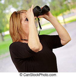 Women looking through binoculars, outdoor
