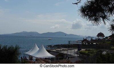 Beautiful coastal scenery & white shed.Cruise boats ships on...