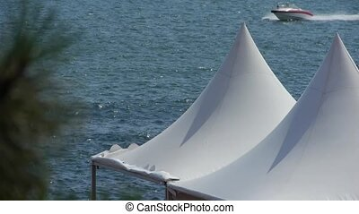 yacht traveling on water ripples surface & white pavilion...