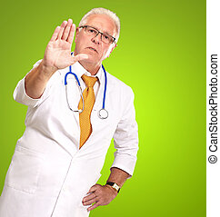Portrait Of A Male Doctor Showing Warning Sign On Green...
