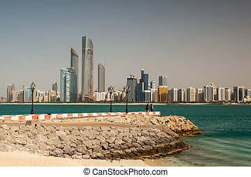 Abu Dhabi panorama - On the empty beach in modern arabic...
