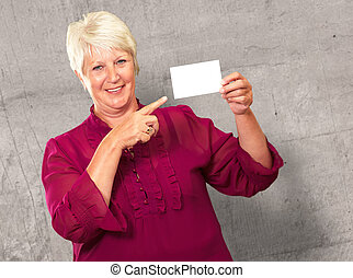 Portrait Of A Senior Woman Pointing To The Blank Card,...