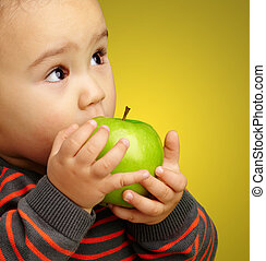 Portrait Of Baby Boy Eating Green Apple against a yellow...