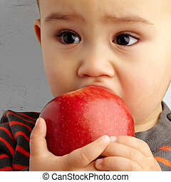 Portrait Of Baby Boy Eating Red Apple against a grunge...