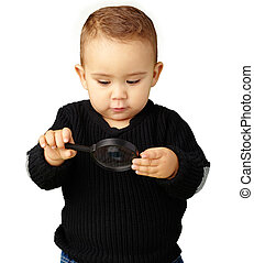 Baby Boy looking at Magnifying Glass Isolated On White...